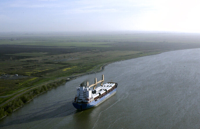 FILE - In this March 12, 2008 file photo, a ship sails through the Sacramento-San Joaquin River Delta near Bethel Island, Calif. California officials announced Thursday, Nov. 21, 2019 that they will sue the Trump administration to block its recently announced rules governing water in the San Joaquin Delta. (AP Photo/Rich Pedroncelli, File)