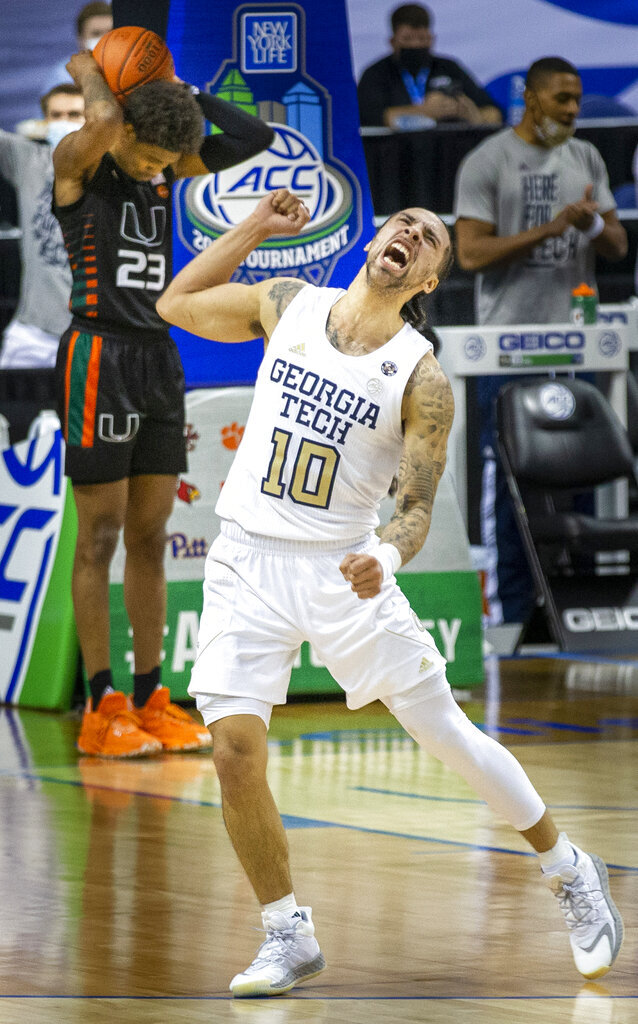 Georgia Tech's Jose Alvarado (10) celebrates as Miami's Kameron McGusty (23) hangs his head after Miami was called for foul late in the second half of an NCAA college basketball game in the quarterfinal round of the Atlantic Coast Conference tournament in Greensboro, N.C., Thursday, March 11, 2021. (Woody Marshall/News & Record via AP)