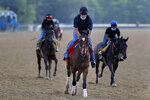 Tap It to Win, center, works out at Belmont Park in Elmont, N.Y., Friday, June 19, 2020. The Belmont Stakes is scheduled to run on Saturday. (AP Photo/Seth Wenig)