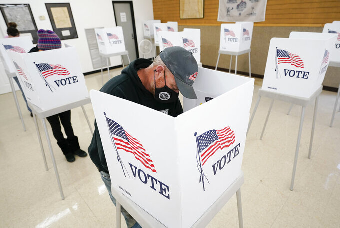 Chris Helps, of Earlham, Iowa, fills out his ballot during early voting, Tuesday, Oct. 20, 2020, in Adel, Iowa. (AP Photo/Charlie Neibergall)