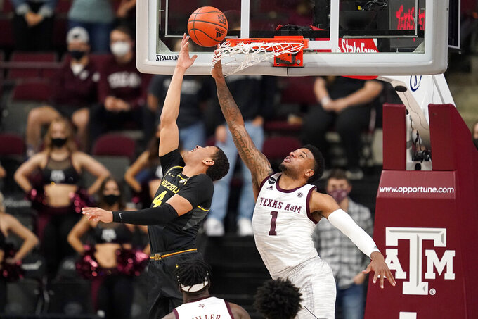 Missouri guard Javon Pickett (4) makes a basket as Texas A&M guard Savion Flagg (1) defends during the second half of an NCAA college basketball game Saturday, Jan. 16, 2021, in College Station, Texas. (AP Photo/Sam Craft)
