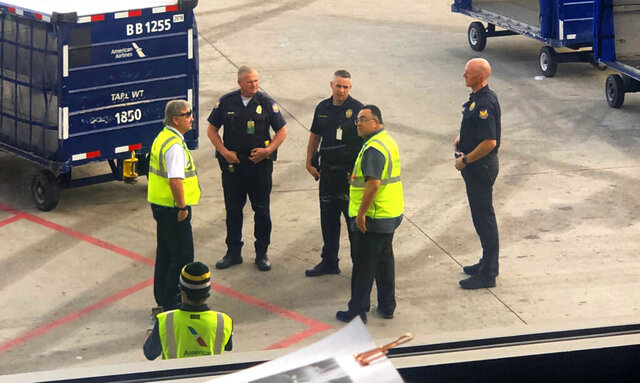 In this Friday, Jan. 24, 2020. photo courtesy of Jim Whitfill, Phoenix police officers are seen on the tarmac of Phoenix Sky Harbor Airport in Phoenix, Ariz. Phoenix police say a woman angry about not being allowed to board a plane at Sky Harbor International Airport was arrested after allegedly mentioning an explosive device, resulting in hundreds of travelers evacuating part of one concourse. No device was found after a search Friday. (Jim Whitfill via AP)