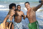 """This image released by Hulu shows Meredith Hagner, from left, Yvonne Orji, Lil Rel Howery and John Cena in a scene from """"Vacation Friends."""" (Jessica Miglio/20th Century Studios)"""