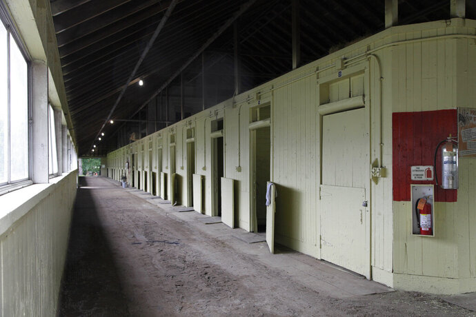 FILE - In this June 4, 2012, file photo, an empty barn at Belmont Park in Elmont, N.Y., is viewed. After a 4-year-old colt exhibited fever and neurological symptoms on Saturday, June 27, 2020, a barn at Belmont Park has been placed under a precautionary quarantine because of a suspected case of equine herpesvirus Type 1. (AP Photo/Mark Lennihan, File)