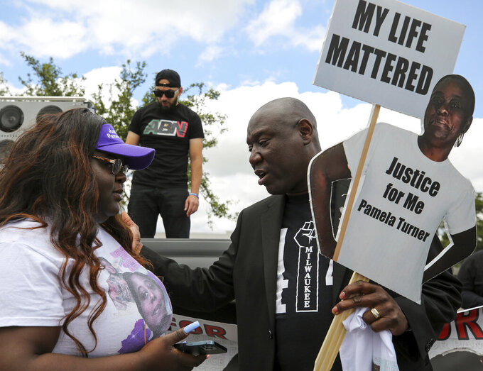 """Attorney Benjamin Crump, right, talks with Chelsie Rubin, daughter of Pamela Turner, before a """"Justice for Pamela Turner"""" rally on the two-year-anniversary of Turner's death, Thursday, May 13, 2021, in Baytown, Texas. Turner was fatally shot in 2019 by a police officer in the Houston suburb after a struggle over his stun gun. (Godofredo A. Vásquez/Houston Chronicle via AP)"""