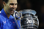 Spain's Rafael Nadal bits the ATP World Number 1 trophy as he poses for photographs following the presentation on court after his match against Stefanos Tsitsipas of Greece at the ATP World Tours Finals in the O2 Arena in London, Friday, Nov. 15, 2019. (AP Photo/Alastair Grant)