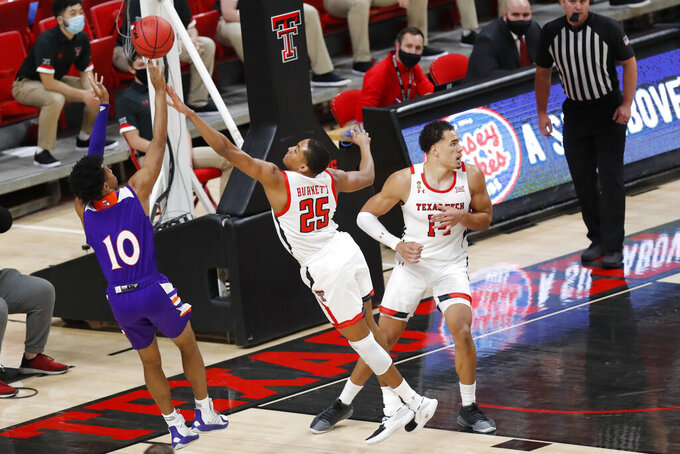 Texas Tech guard Nimari Burnett tries to block a shot by Northwestern State guard Jairus Roberson during the first half of an NCAA college basketball game Wednesday Nov. 25, 2020, in Lubbock, Texas. (AP Photo/Mark Rogers)