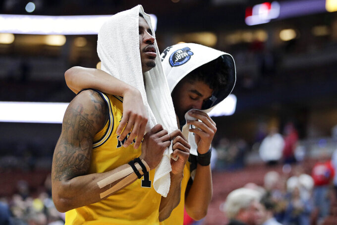 Michigan guard Charles Matthews, left, and guard Jordan Poole leave the court after the team's loss to Texas Tech during an NCAA men's college basketball tournament West Region semifinal Thursday, March 28, 2019, in Anaheim, Calif. (AP Photo/Jae C. Hong)