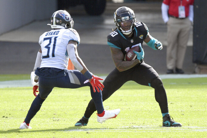 Jacksonville Jaguars wide receiver Laviska Shenault Jr. (10) tries to get past Tennessee Titans safety Kevin Byard (31) after a reception during the first half of an NFL football game, Sunday, Dec. 13, 2020, in Jacksonville, Fla. (AP Photo/Phelan M. Ebenhack)