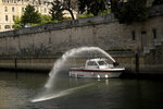 Firefighters work with a hose on a boat at the Seine river near the Notre Dame cathedral in Paris, Thursday, April 18, 2019. France is paying a daylong tribute Thursday to the Paris firefighters who saved the internationally revered Notre Dame Cathedral from collapse and rescued its treasures from encroaching flames. (AP Photo/Francisco Seco)