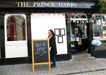 A publican displays a board outside the Prince Harry pub, in Windsor, south England, Tuesday, May 7, 2019, a day after Prince Harry announced that his wife Meghan, Duchess of Sussex, had given birth to a boy.The as-yet-unnamed baby arrived less than a year after Prince Harry wed Meghan Markle in a spectacular televised event on the grounds of Windsor Castle that was watched the world over. (AP Photo/Alastair Grant)