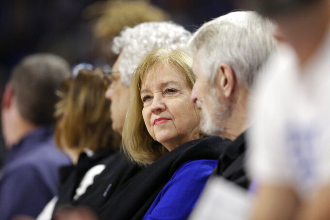 FILE - In this Nov. 17, 2019, file photo, St. Louis Mayor Lyda Krewson sits during an NCAA college basketball game between Saint Louis and Seton Hall in St. Louis. Krewson was elected on a pledge to address the violence that ravages her city. Amid that backdrop, it's not surprising that calls to defund police don't sit well with her. Yet Krewson's decision to publicly reveal the names and addresses of anti-police protesters has put her among the big city mayors facing closer scrutiny in the racially charged weeks after George Floyd's death. (AP Photo/Jeff Roberson, File)