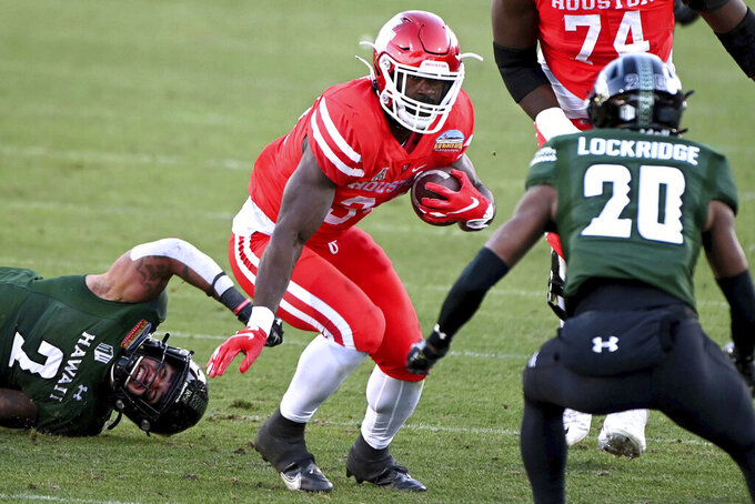 Houston running back Mulbah Car (34) looks for running room between Hawaii linebacker Jeremiah Pritchard (2) and defensive back Cameron Lockridge (20) in the third quarter of the New Mexico Bowl NCAA college football game in Frisco, Texas, Thursday, Dec. 24, 2020. (AP Photo/Matt Strasen)