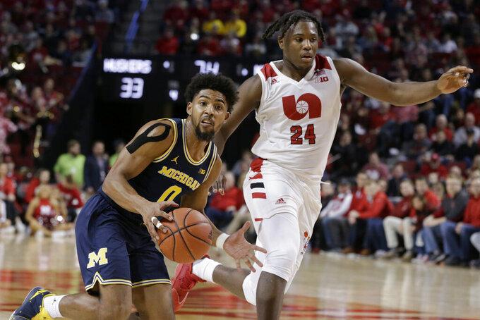 Michigan's David DeJulius (0) drives around Nebraska's Yvan Ouedraogo (24) during the first half of an NCAA college basketball game in Lincoln, Neb., Tuesday, Jan. 28, 2020. (AP Photo/Nati Harnik)