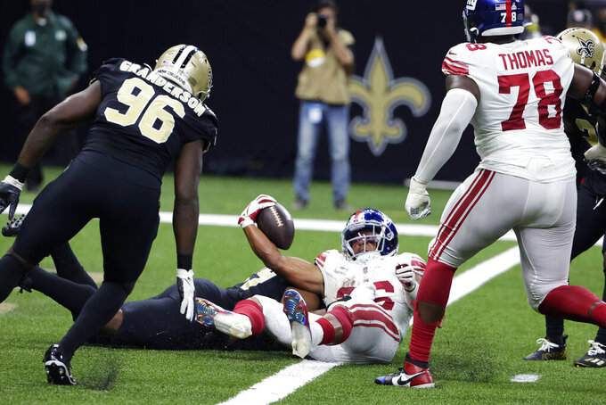 New York Giants running back Saquon Barkley (26) scores a touchdown against New Orleans Saints defensive end Carl Granderson (96) and defensive tackle Shy Tuttle to win in overtime during an NFL football game in New Orleans, Sunday, Oct. 3, 2021. The Giants won 27-21. (AP Photo/Derick Hingle)