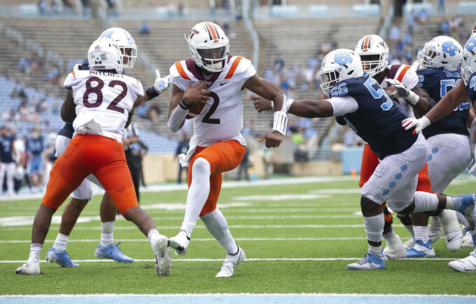 Virginia Tech quarterback Hendon Hooker (2) scores pas North Carolina's Tomari Fox (56) on a five-yard carry in the third quarter of an NCAA college football game, Saturday, Oct. 10, 2020 at Kenan Stadium in Chapel Hill, N.C. (Robert Willett/The News & Observer via AP)