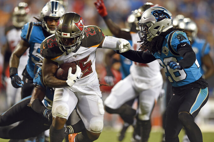 Tampa Bay Buccaneers running back Peyton Barber (25) runs for a touchdown while Carolina Panthers cornerback Donte Jackson (26) looks to tackle during the second half of an NFL football game in Charlotte, N.C., Thursday, Sept. 12, 2019. (AP Photo/Mike McCarn)