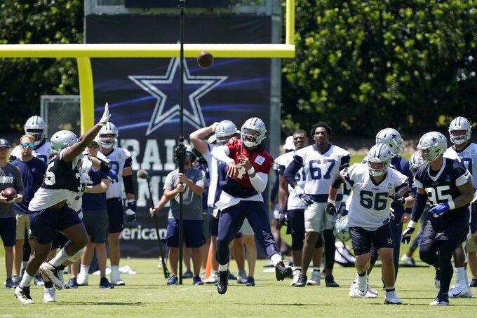 Dallas Cowboys quarterback Dak Prescott, center, throws a pass during workouts at the team's NFL football training facility in Frisco, Texas, Wednesday, Aug. 25, 2021. (AP Photo/Tony Gutierrez)
