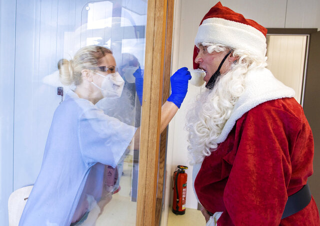FILE - In this Dec. 21, 2020, file photo, Tessa Boulton, left, takes a swab test from Michael Kruse, dressed as Santa Claus, at a coronavirus testing center at the Helios Clinic in Schwerin, Germany. All most people wanted for Christmas after this year of pandemic was some cheer and togetherness. Instead many are heading into a season of isolation, grieving lost loved ones, experiencing uncertainty about their jobs or confronting the fear of a potentially more contagious variant of the coronavirus. (Jens Buettner/dpa via AP, File)