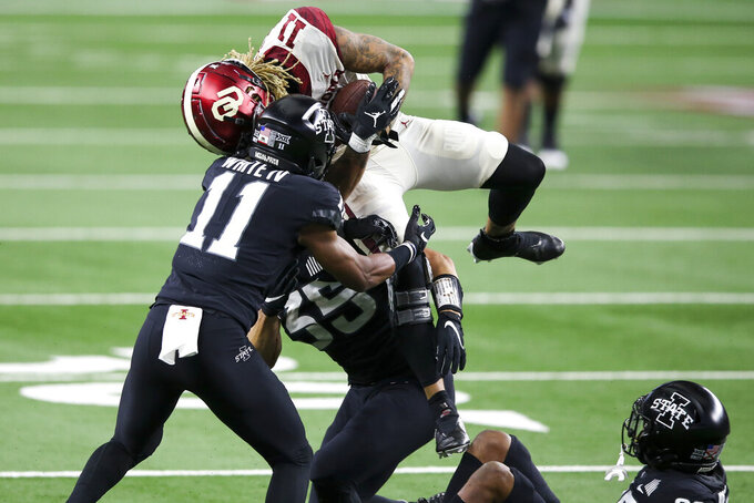 Oklahoma wide receiver Jadon Haselwood (11) secures a catch while being hit by Iowa State defensive back Lawrence White IV (11) and linebacker Jake Hummel (35) during the first half of the the Big 12 Conference championship NCAA college football game, Saturday, Dec. 19, 2020, in Arlington, Texas. (Ian Maule/Tulsa World via AP)