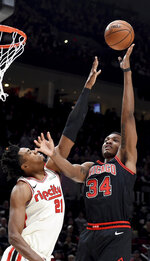 Chicago Bulls center Wendell Carter Jr., right, shoots the ball over Portland Trail Blazers center Hassan Whiteside during the first quarter of an NBA basketball game in Portland, Ore., Friday, Nov. 29, 2019. (AP Photo/Steve Dykes)