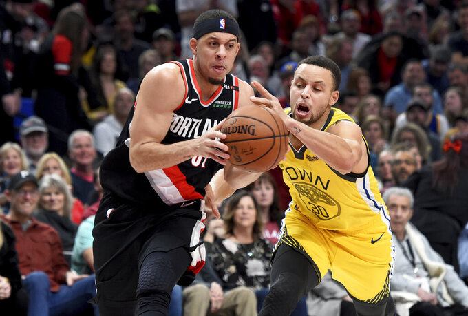 Portland Trail Blazers guard Seth Curry, left, drives to the basket on Golden State Warriors guard Stephen Curry during the second half of an NBA basketball game in Portland, Ore., Wednesday, Feb. 13, 2019. The Blazers won 129-107. (AP Photo/Steve Dykes)
