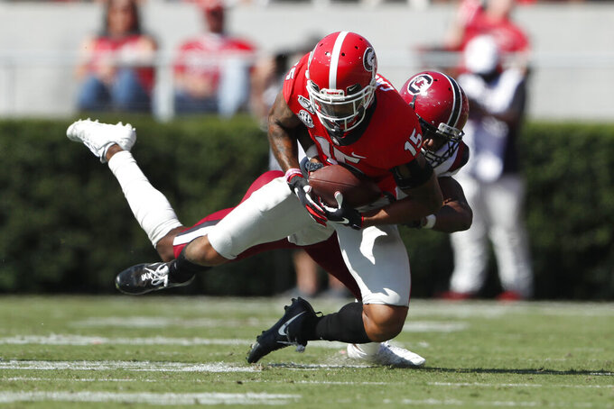 Georgia wide receiver Lawrence Cager (15) makes a catch as South Carolina defensive back Jaycee Horn (1) defends in the first half of an NCAA college football game Saturday, Oct. 12, 2019, in Athens, Ga. (AP Photo/John Bazemore)