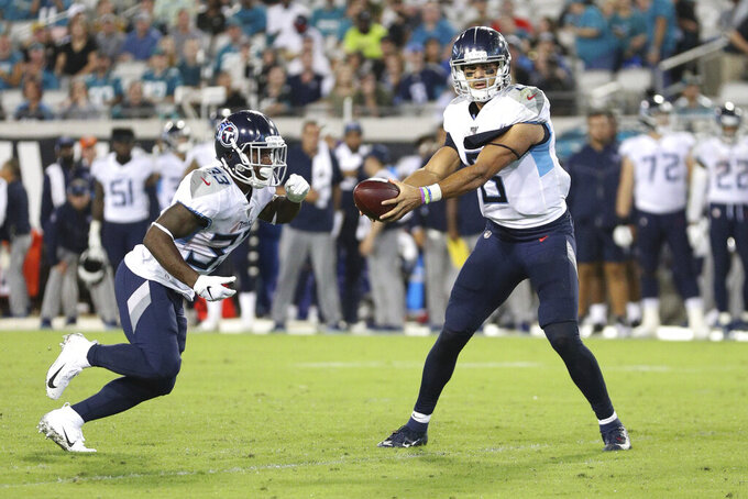 Tennessee Titans quarterback Marcus Mariota (8) prepares to hand the ball off to Tennessee Titans running back Dion Lewis (33 during an NFL game against the Jacksonville Jaguars, Thursday, Sept. 19, 2019, in Jacksonville, Fla. The Jaguars defeated the Titans 20-7. (Margaret Bowles via AP)