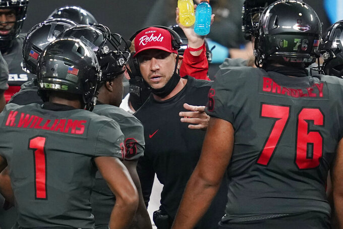 UNLV head coach Marcus Arroyo speaks with his players during the second half of an NCAA college football game against Nevada, Saturday, Oct. 31, 2020, in Las Vegas. (AP Photo/John Locher)