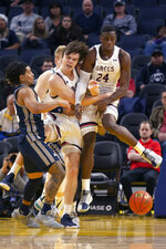 Nevada guard Jazz Johnson, left, Saint Mary's forwards Alex Ducas (44) and Malik Fitts (24) collide chasing a rebound during the first half of an NCAA college basketball game on Saturday, Dec. 21, 2019, in San Francisco. (AP Photo/D. Ross Cameron)