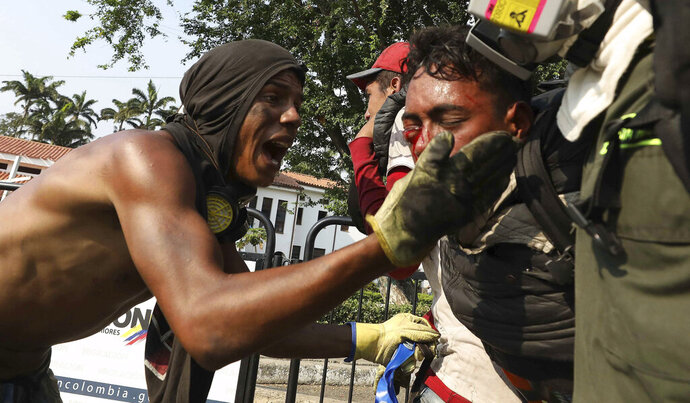 A youth, right, who was injured in clashes with Venezuelan National Guardsmen, who are blocking the entry of U.S.-supplied humanitarian aid on the Simon Bolivar International Bridge, is carried by medics to a safe zone in La Parada, Colombia, Monday, Feb. 25, 2019, on the border with Venezuela. The delivery of humanitarian aid to the economically devastated nation has faltered amid strong resistance from security forces who remain loyal to Venezuelan President Nicolas Maduro. (AP Photo/Fernando Vergara)