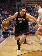 Houston Rockets forward Ryan Anderson (33) drives past Phoenix Suns forward Dragan Bender during the first half of an NBA basketball game Friday, Jan. 12, 2018, in Phoenix. (AP Photo/Matt York)