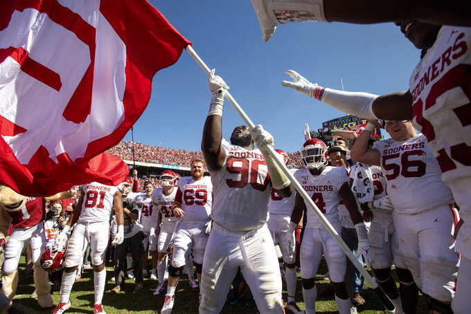 FILE - In this Oct. 12, 2019, file photo, Oklahoma defensive lineman Neville Gallimore (90) waves an OU flag after his team's 34-27 victory over Texas in an NCAA college football game at the Cotton Bowl in Dallas. The Texas and Oklahoma college football matchup will be a different game-day atmosphere this year with small crowds, no State Fair, a few food vendors, masks and social distancing. (AP Photo/Jeffrey McWhorter, File)