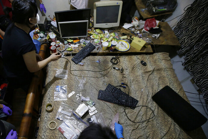 FILE - In this April 20, 2017, file photo, members of the National Bureau of Investigation and FBI gather evidence at the home of an American suspected child webcam cybersex operator during a raid in Mabalacat, Philippines. The Philippines has emerged as a global hot spot for online child sexual exploitation, and coronavirus lockdowns that restrict millions to their homes may be worsening the abuses, a U.S. official said Thursday, May 21, 2020. (AP Photo/Aaron Favila, File)