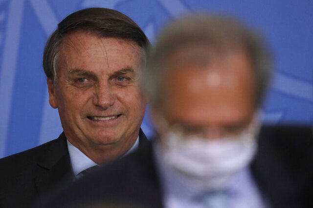 Brazil's President Jair Bolsonaro smiles behind his Economy Minister Paulo Guedes during a ceremony on a program to increase public sector efficiency at the Planalto presidential palace, in Brasilia, Brazil, Thursday, Nov. 26, 2020 (AP Photo/Eraldo Peres)