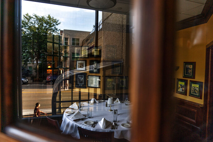 A set table sits empty inside the closed Vince Lombardi's Steakhouse in Appleton, Wis., Aug. 20, 2020. Appleton is testimony to the lack of simple solutions to the coronavirus pandemic. Nearly 40% of the city's leisure and hospitality jobs have been lost. Restaurants have been closed, hotels vacant. (AP Photo/David Goldman)