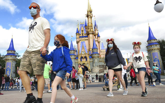 FILE - In this Monday, Dec. 21, 2020, file photo, a masked family walks past Cinderella Castle in the Magic Kingdom, at Walt Disney World in Lake Buena Vista, Fla. Walt Disney World is tweaking its face mask policy. Starting Thursday, Aug. 19, 2021, the theme park resort in Florida will allow visitors to chose whether or not to wear face coverings in outdoor lines, outdoor theatres and outdoor attractions. (Joe Burbank/Orlando Sentinel via AP, File)