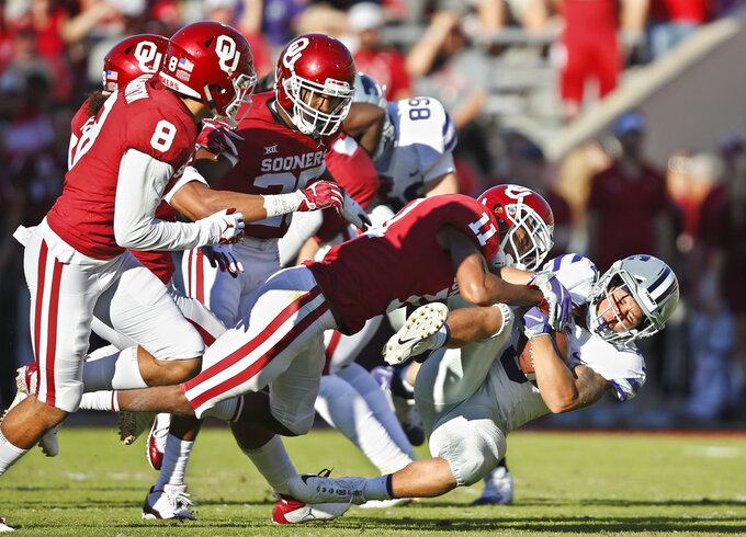 Kansas State running back Dalvin Warmack (3) is tackled by Oklahoma cornerback Parnell Motley (11) in the second half of an NCAA college football game in Norman, Okla., Saturday, Oct. 27, 2018. (AP Photo/Sue Ogrocki)