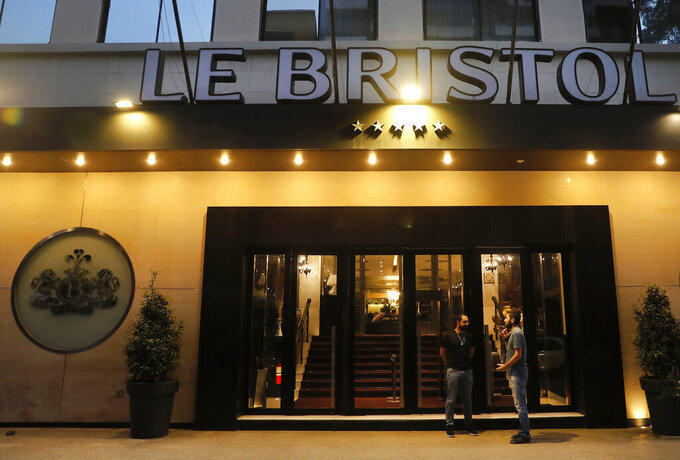 Two men talk at the entrance of Le Bristol hotel, in Beirut, Lebanon, Saturday, April 18, 2020. Le Bristol, one of Lebanon's landmark hotels that has survived the country's bloody 15-year civil war is folding, closing its doors in the face of a combination of an economic crisis and the global health threat of the coronavirus, one of its executives said Saturday. (AP Photo/Hussein Malla)