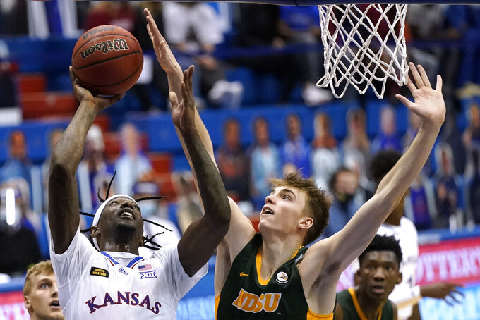 Kansas' Marcus Garrett, left, shoots under pressure from North Dakota State's Grant Nelson during the second half of an NCAA college basketball game Saturday, Dec. 5, 2020, in Lawrence, Kan. Kansas won 65-61. (AP Photo/Charlie Riedel)