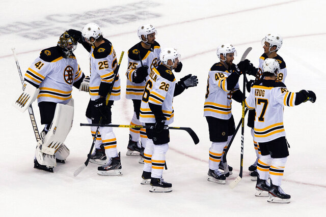 Boston Bruins' Brandon Carlo (25) congratulates goaltender Jaroslav Halak as teammates celebrate their victory over the Carolina Hurricanes in NHL Eastern Conference Stanley Cup playoff game in Toronto on Saturday, Aug. 15, 2020.  (Chris Young/The Canadian Press via AP)