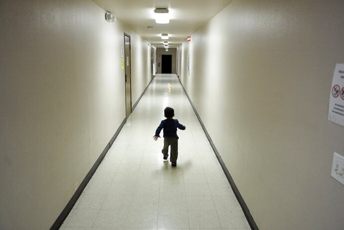FILE - In this Dec. 11, 2018 file photo, an asylum-seeking boy from Central America runs down a hallway after arriving from an immigration detention center to a shelter in San Diego. A federal judge said Friday, Sept. 20, 2019, that he was struggling with a request to more narrowly define what behavior justifies separating children from their parents at the border after complaints that the Trump administration has abused discretionary powers to split families under limited circumstances, like criminal history or questions about whether the adult is really the parent. (AP Photo/Gregory Bull, File)