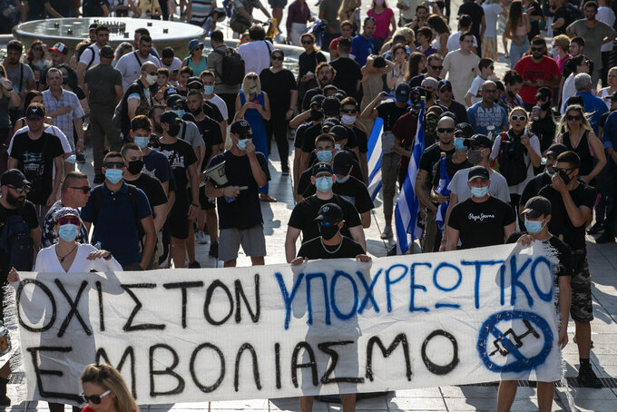 """Anti-vaccine protesters hold a banner during a rally at Syntagma square, central Athens, on Wednesday, July 21, 2021. Thousands of people protested against Greek government's measures to curb rising COVID-19 infections and drive up vaccinations in the country where almost 50% of Greeks and country residents have received at least one dose of the vaccine. The banner reads :"""" No to mandatory vaccination"""". (AP Photo/Yorgos Karahalis)"""