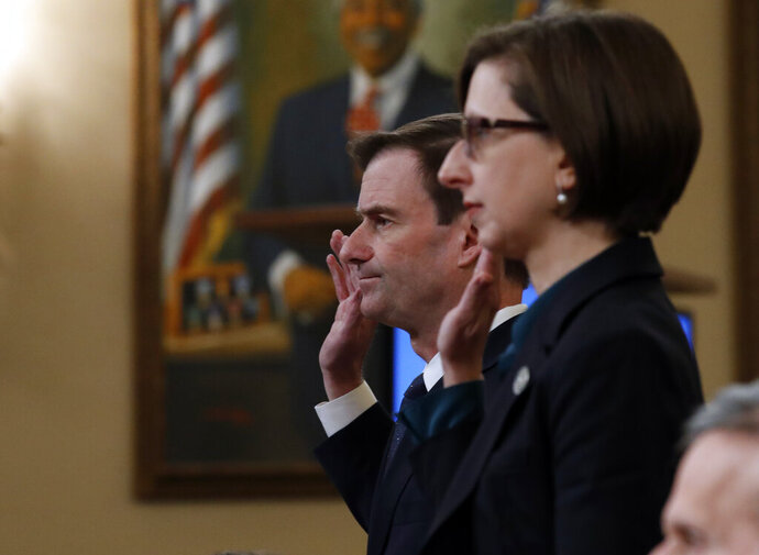 Deputy Assistant Secretary of Defense Laura Cooper, right, and State Department official David Hale, are sworn in to testify before the House Intelligence Committee on Capitol Hill in Washington, Wednesday, Nov. 20, 2019, during a public impeachment hearing of President Donald Trump's efforts to tie U.S. aid for Ukraine to investigations of his political opponents. (AP Photo/Alex Brandon)