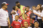 Legendary Boston Red Sox slugger David Ortiz poses for a photo with with youth from the David Ortiz Children's Fund after making a surprise appearance at the Day of Legends baseball event at the Quisqueya Stadium, in Santo Domingo, Dominican Republic, Sunday, Dec. 8, 2019. The Dominican-American retired professional baseball player was shot in the back in his native country six months ago by a hired gunman who drove up on a motorcycle and fired at close range, hitting him in the torso. They said the intended target was another man. (AP Photo/Tatiana Fernandez)