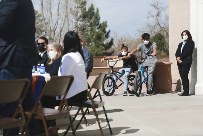 In this Monday, April 5, 2021, photo Jonathan Chilton, 14, center, sits on his BMX bike in front of the New Mexico state capitol ahead of a bill signing by the governor in Santa Fe, N.M. Chilton started school remotely on Tuesday following the Easter break. Around half of his classmates are now studying in-person, and he's not sure if he should go back with just a few weeks left in the semester. (AP Photo/Cedar Attanasio)