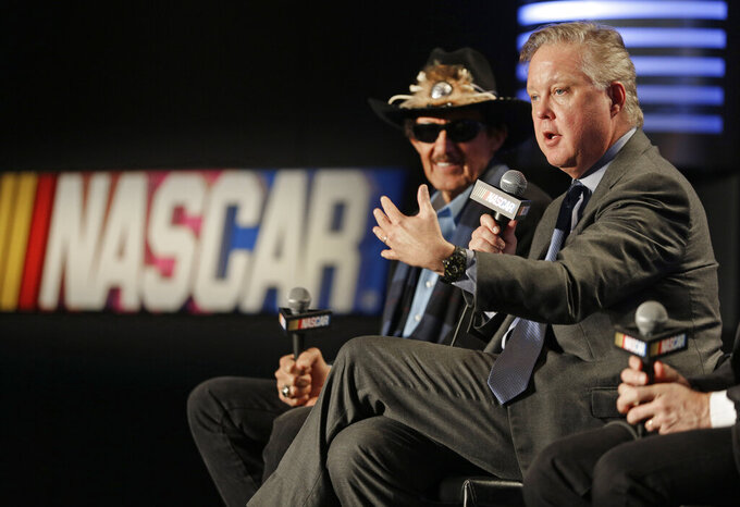 FILE - NASCAR Chairman and CEO Brian France, right, speaks as team owner Richard Petty, left, listens during a news conference to announce a new charter system for team owners in Charlotte, N.C., in this Tuesday, Feb. 9, 2016, file photo. A charter is essentially the same as a franchise and the 36 that exist both guarantee a spot in the 40-car field each week as well as a larger slice of the money NASCAR contractually owes its participants. (AP Photo/Chuck Burton, File)