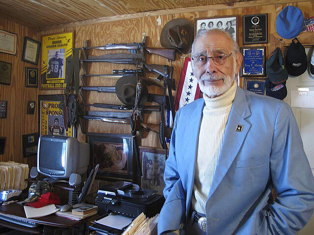 In this March 11, 2013 photo, Benny Martinez, a Mexican American civil rights leader who helped organize the historic Latino gala with President John F. Kennedy, stands in front of a gun collection at his Goliad, Texas, home. Martinez, 85, died Sunday, Dec. 29, 2019, of natural causes. (AP Photo/Russell Contreras)