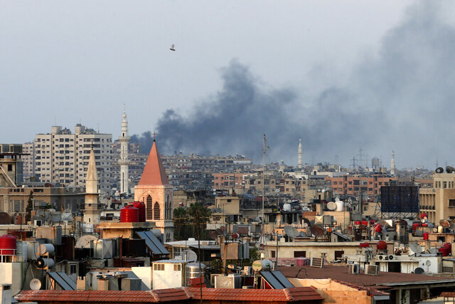 FILE - In this Thursday, Aug. 22, 2013 file photo, smoke rises from heavy shelling in the Jobar neighborhood in Damascus, Syria, seen from Cairo.  Human rights groups have filed a criminal complaint in Germany that asks prosecutors to investigate two chemical weapons attacks in Syria. Three groups want Germany's attorney general to probe the deadly sarin attacks on the Damascus suburb of Eastern Ghouta and the town of Khan Shaykhun that occurred in 2013 and 2017 respectively. (AP Photo/Hassan Ammar, File)