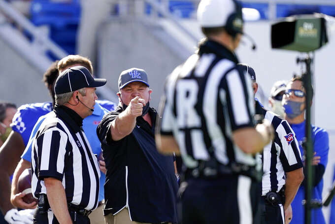 FILE - In this Saturday, Oct. 3, 2020, file photo, Kentucky head coach Mark Stoops points at an official during the first half of an NCAA college football game against Mississippi in Lexington, Ky. Sloppy play has been common over the first few weeks of the season, and much of it has been attributed to there having been little or no spring practice and disrupted summer workouts and preseason practices. As a result, game officials' preparation also was impacted. They typically hone their craft at game speed by working live scrimmages in the spring and preseason. There weren't nearly as many opportunities this year. (AP Photo/Bryan Woolston, file)